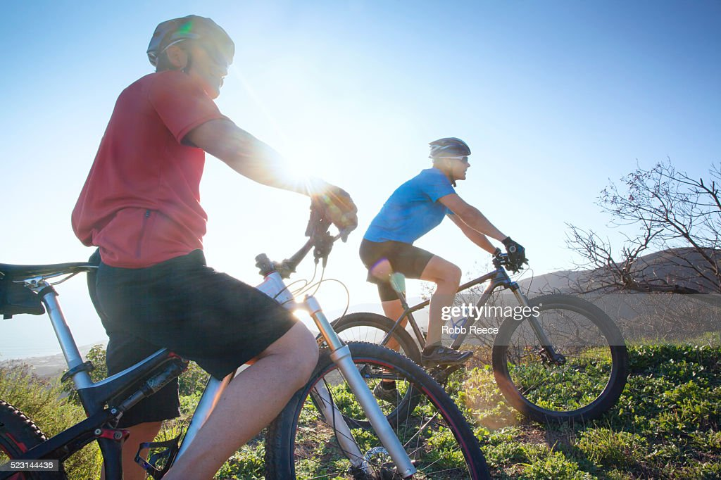 Two adult men getting ready to ride mountain bikes up a steep trail on a hill : Stock Photo