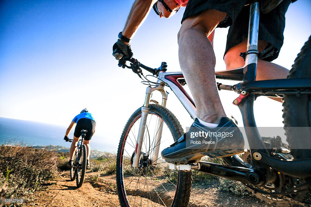 Two adult men riding mountain bikes on a steep, hilly trail above the ocean : Stock Photo