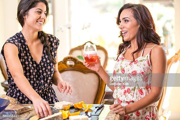 Two adult sisters drinking rose wine and snacking from cheeseboard