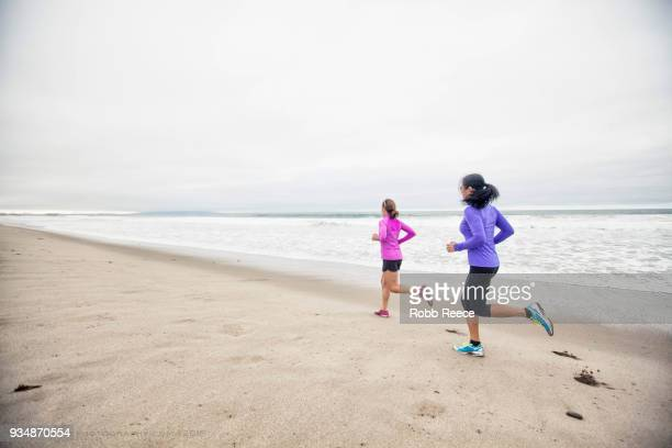 two adult woman running in the sand on a remote beach - robb reece stockfoto's en -beelden