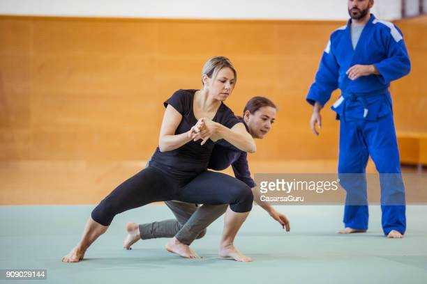 Two Adult Women Practicing Self Defense Against Collar Grab With Judo Trainer
