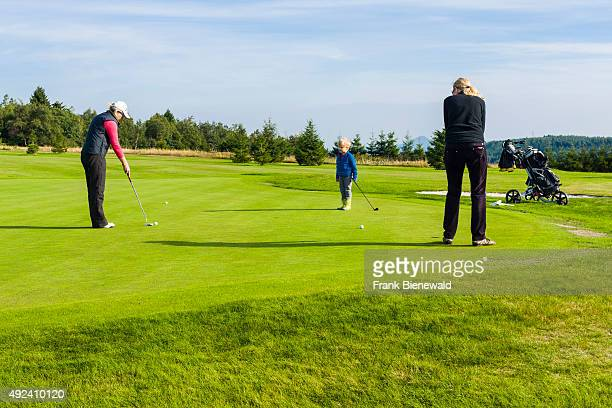 Two adults and a child are playing golf on a golf course