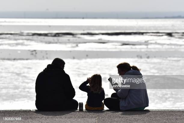 Two adults and a child sit by the beach on a warm sunny day as the weather warms for the week ahead on February 21, 2021 in Southend, England....