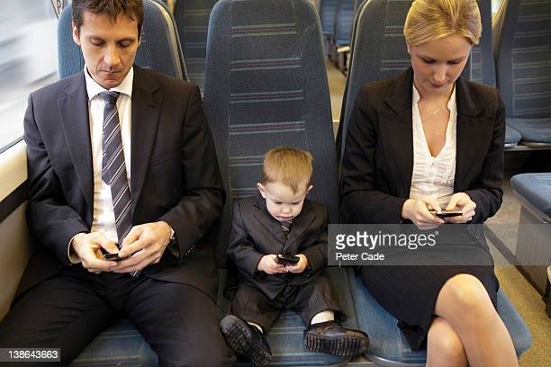 two adults and one baby executive sat on train