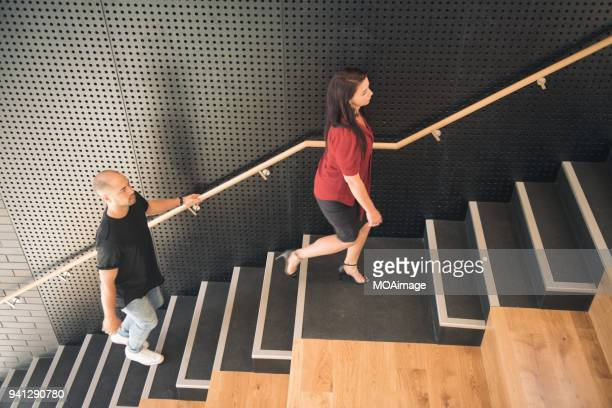 Two adults are going up the stairs