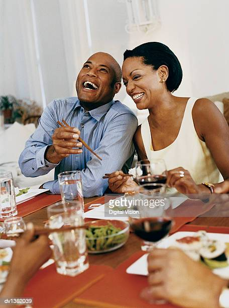 Two Adults Laughing as They Sit at a Table Eating Sushi
