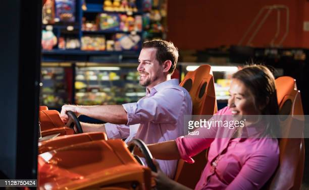 two adults playing driving game in video arcade - arcade stock photos and pictures