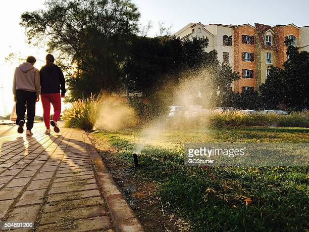 two adults walking on society footpath - healthy lifestyle - sprinkler system stock pictures, royalty-free photos & images