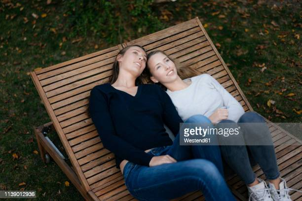 two affectionate thoughtful teenage girls resting on sun lounger - chaise longue photos et images de collection