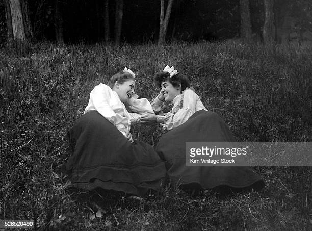 Two affectionate women sprawl on the North Dakota grass and look into each others eyes.