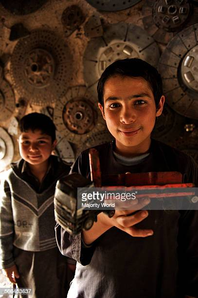 Two Afghan boys at an automobile workshop in the northwestern city of Herat Afghanistan May 6 2009 Young boys who join as 'shagrid' at the sweatshops...