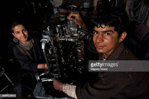 Two Afghan boys at an automobile workshop in the northwestern city of Herat Afghanistan May 6 2009 Young boys who join as '˜shagrid' at the...