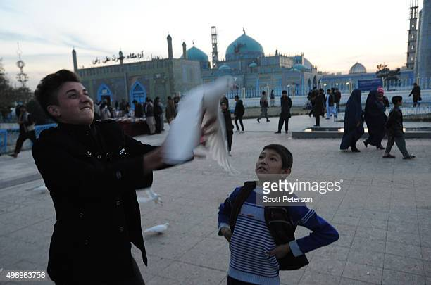 Two Afghan boys release a pigeon beside the ancient Blue Mosque as Afghans go about daily life despite security fears of a resurgent Taliban on...