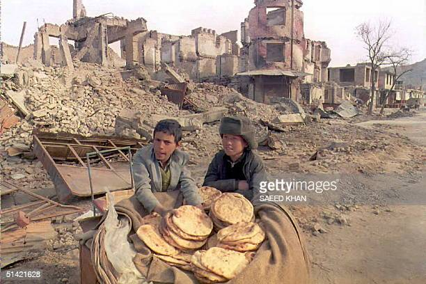 Two Afghan children sell Nan bread near the ruins of a former shopping boulevard in eastern Kabul 21 February an area which was the site of frontline...