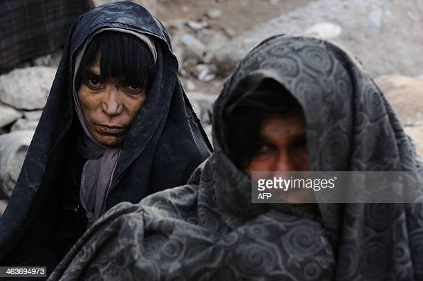 Two Afghan drug addict women look on in the city of Herat on January 18 2014 Afghanistan is the source of over 90 percent of the illicit opium in the...