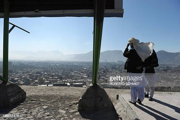Two Afghan friends from childhood look at the city below at a hilltop park overlooking Kabul on December 16 2011 The men decided to come to the park...