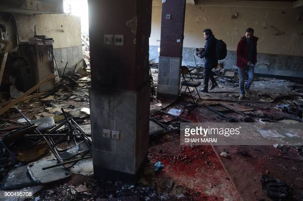 Two Afghan journalists take pictures at the site of explosions at a Shiite cultural centre in Kabul on December 28 2017 Around 40 people were killed...
