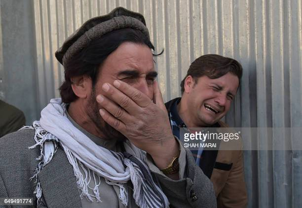 TOPSHOT Two Afghan men weep for their relatives in front of the main gate of a military hospital in Kabul on March 8 after a deadly sixhour attack...