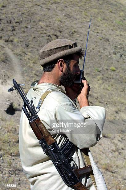 Two Afghan Northern Alliance fighters listen to a radio at the front line against the Taliban October 2, 2001 near Jabul os Sarache, 30 miles north...