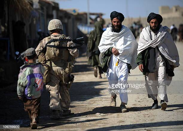 Two Afghan residents walk past US Marines 2nd Batallion1st Marines Regiment during a patrol in Gamser Helmand province southern Afghanistan on...