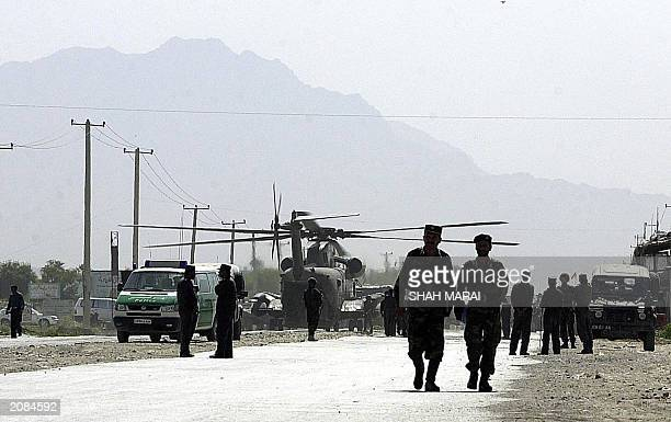 Two Afghan security personnel walk away from the spot of a blast in Kabul, 07 June 2003. Six people including three German soldiers were killed and...