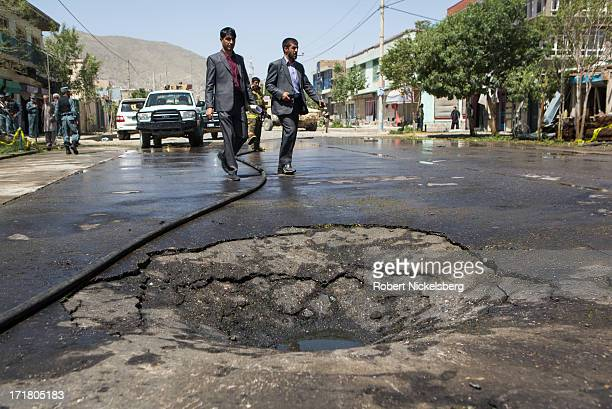 Two Afghan security personnel walk past the crater left behind by a suicide bomb explosion May 16, 2013 in Kabul, Afghanistan. Sixteen people were...