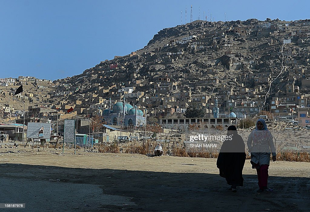 Two Afghan women walk in a cemetery outside The Kart-e-Sakhi shrine in Kabul on December 11, 2012. Afghanistan has made some progress in using the law to protect women against violence but many still suffer horrific abuse at the hands of men, a UN report said on December 11. AFP PHOTO/ SHAH Marai