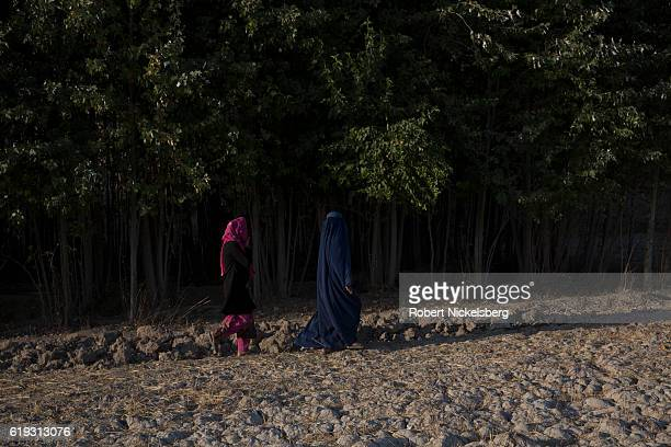 Two Afghan women walk on a path on the edge of a farm field near the Old Balkh City Wall in Balkh Province Afghanistan September 15 2016