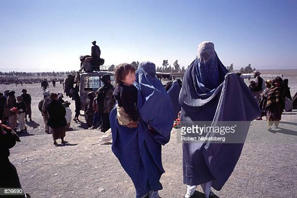 Two Afghan women walk toward their shelter after a 17 km bus ride from Herat city February 25 2001 at the Maslakh refugee camp for newly arrived IDP...