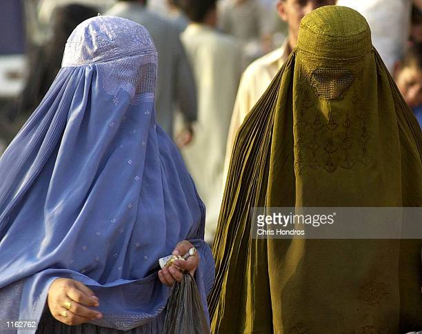 Two Afghan women wearing burqas walk in the Nasser Bagh refugee camp September 26 2001 in Peshawar Pakistan Millions of Afghan refugees are already...
