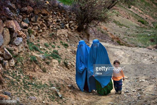 Two Afghan women wearing burqas walking with a little girl along a Sefid Shir's road May 12 2009 in Sefid Shir Village Afghanistan