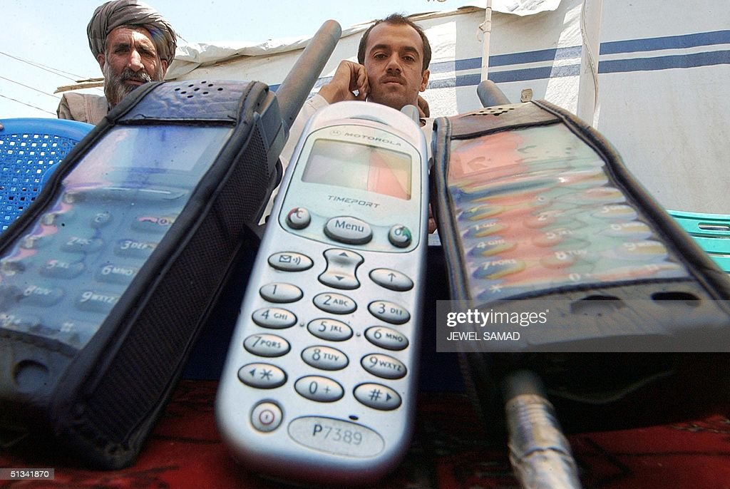 3a288689a937 Two Afghans display mobile phone units as they await for customers at their  open air shop