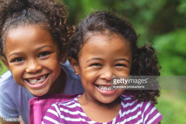 Two African American Chinese Ethnicity sisters posing for portrait in lush green outdoor back yard setting