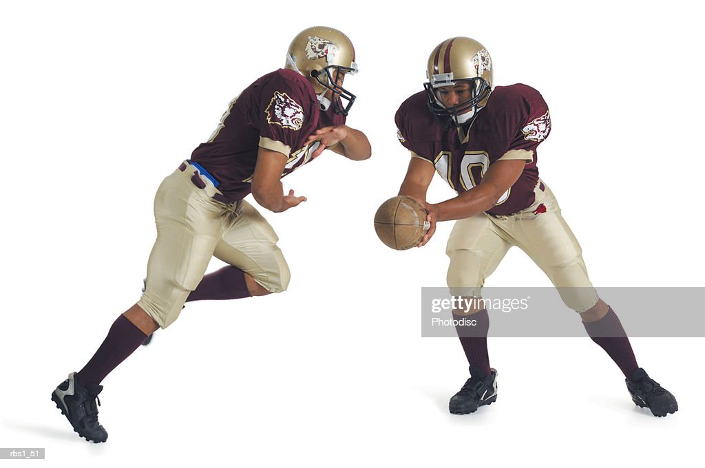 two african american football players wearing red and white uniforms are running towards each other as one prepares to pass the ball to the other : Foto de stock
