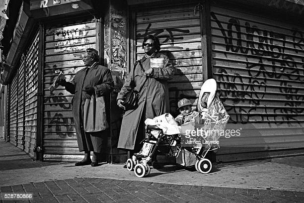 Two African American women both Jehovah's Witnesses and a young boy in a baby carriage stand on a street corner in Harlem in front of a boarded up...