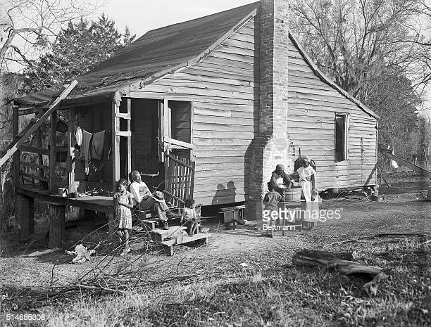 Two African American women wash clothes in the yard of a form slave shack on a Natchez Mississippi plantation Their younger children play nearby and...