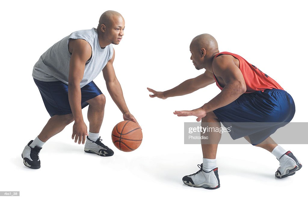 two african american young men are dressed in opposing team basketball uniforms as one dribbles a basketball and the other attempts to steal it : Foto de stock
