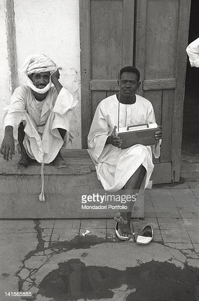 Two African boys seated on a bench on the pavement outside the door of a dwelling passing the time listening to a transistor radio the radio a...