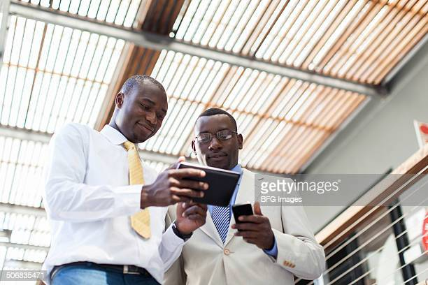 Two african business men using a digital tablet, Cape Town, South Africa