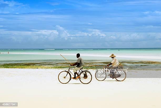 Two African fisherman  cycling on Kiwengwa Beach, Zanzibar,Tanzania