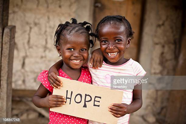 Two African little girls holding a board that says HOPE