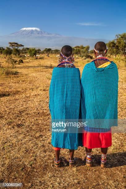 zwei afrikanische frauen aus dem masai-stamm mit blick auf den kilimandscharo, kenia, ostafrika - afrikanischer volksstamm stock-fotos und bilder