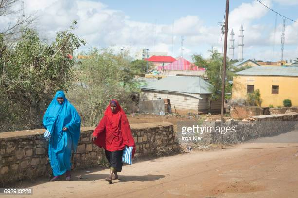 Two African women walk along a street Street scene in Baidoa on May 01 2017 in Baidoa Somalia