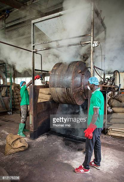 Two African workers of the MIM cashew processing company operate a machine in which cashew nuts are roasted on September 07 2016 in Mim Ghana