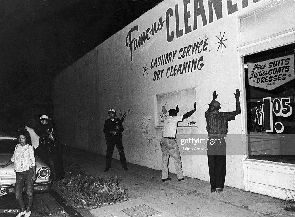 Two African-American men hold their hands up against the wall of a dry cleaners while being arrested by Caucasian state troopers during the Watts race riots, Los Angeles, California.