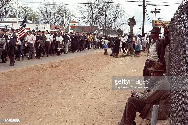 Two AfricanAmerican men in foreground leaning against fence and watching 1965 Selma to Montgomery Alabama line of civil rights marchers On March 25...