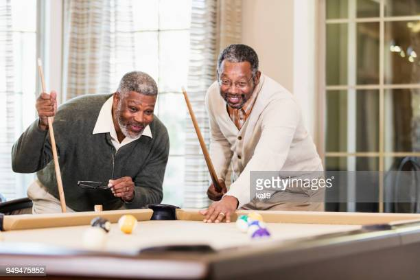 Two African-American men playing billiards
