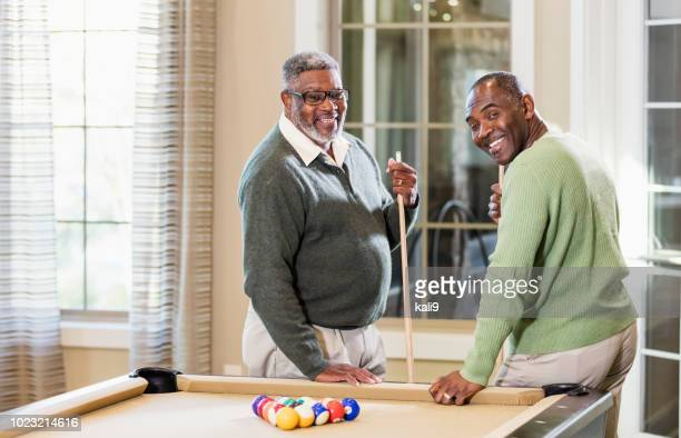 two african-american men shooting pool - fat black man stock photos and pictures