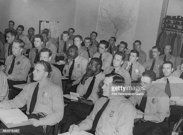 Two African-American police officers set among a crowd of Caucasian officers while in class following their induction into the Washington, DC police,...