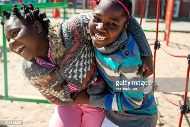 "two african-american twin girls playing in school playground at recess.. - ""martine doucet"" or martinedoucet stock pictures, royalty-free photos & images"